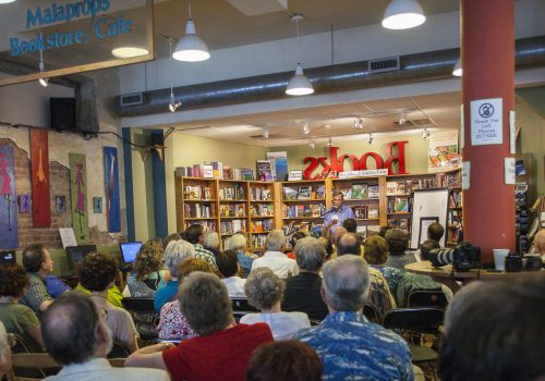 People sitting listening to a reading at Malaprop's Bookstore